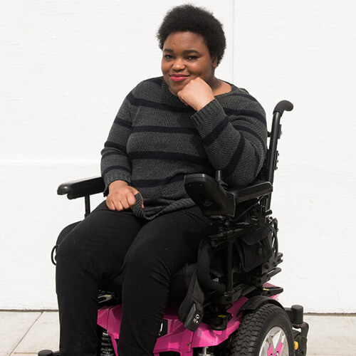 A Black non-binary person in a black and pink power wheelchair.
