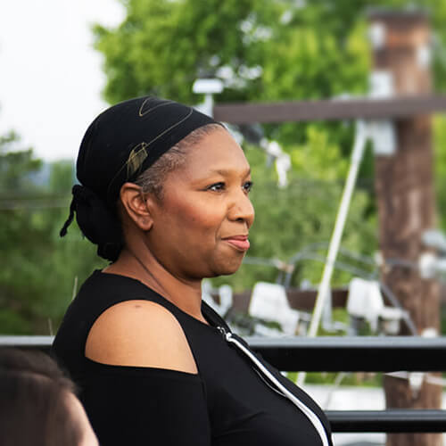 A Black woman wearing a head scarf sits on a rooftop deck, smiling and looking off to the side.
