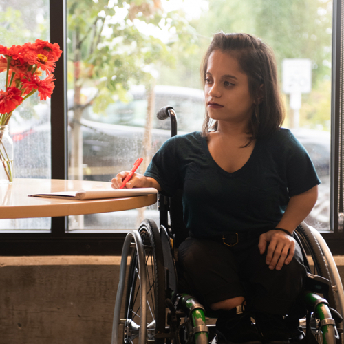 A South Asian person sits in a wheelchair and gazes off-camera.